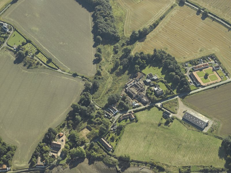 Oblique aerial view centred on the remains of the abbey and church and the farmsteading with the remains of the church and burial-ground adjacent, taken from the NW.
