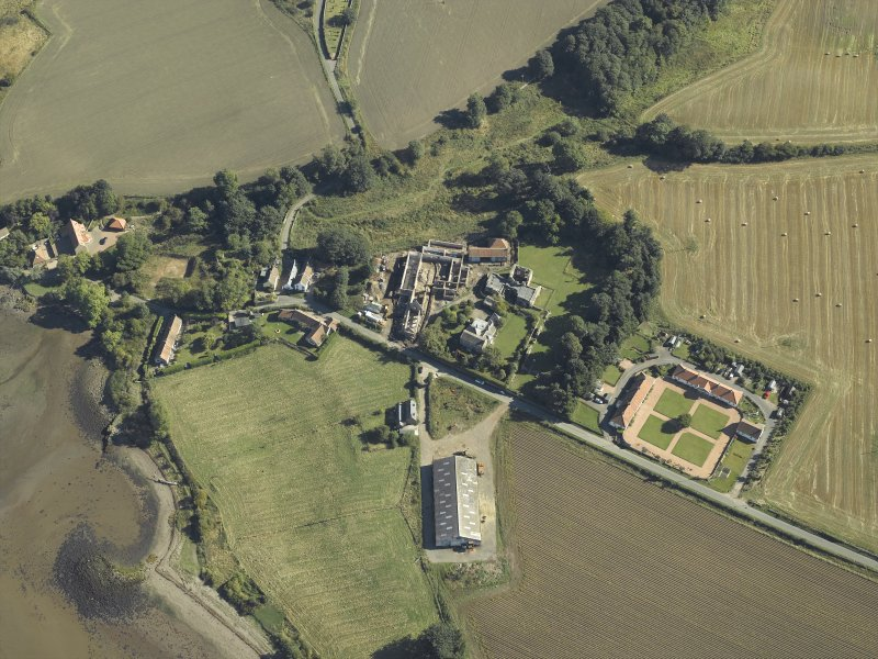Oblique aerial view centred on the remains of the abbey and church and the farmsteading, taken from the WSW.