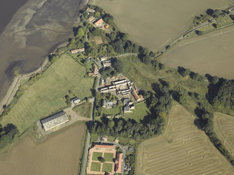 Oblique aerial view centred on the remains of the abbey and church and the farmsteading with the remains of the church and burial-ground adjacent, taken from the S.