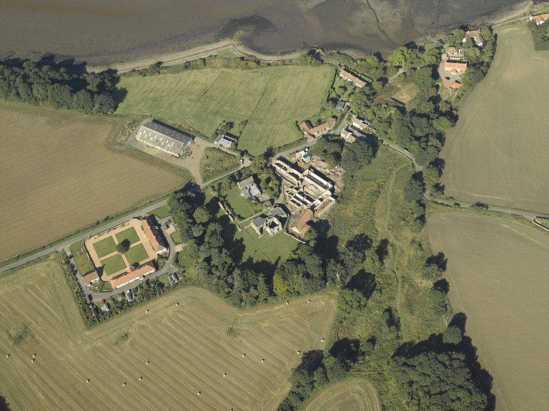 Oblique aerial view centred on the remains of the abbey and church and the farmsteading, taken from the ESE.
