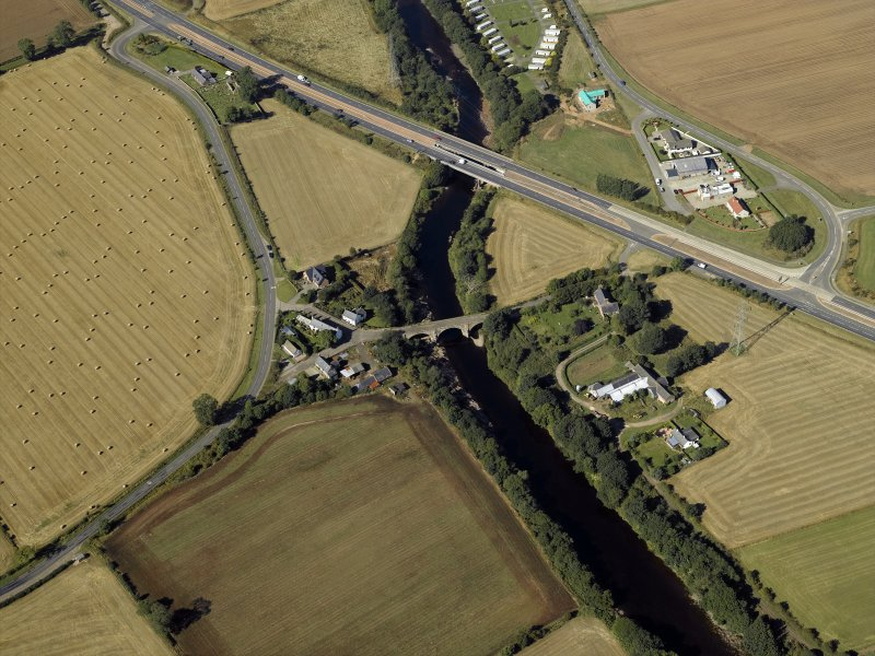 Oblique aerial view centred on the road bridges and tollhouse with the church and burial ground adjacent, taken from the E.