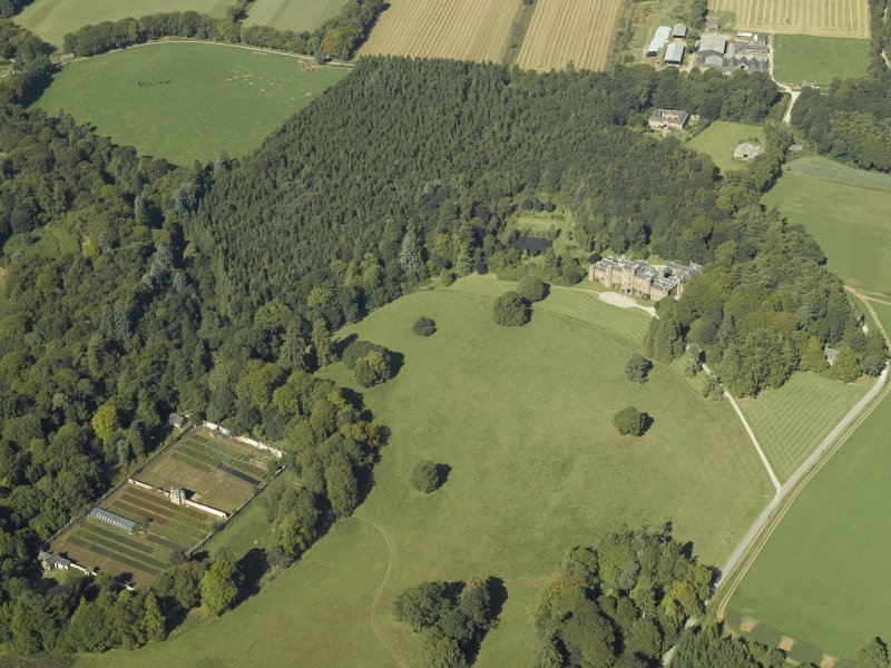 General oblique aerial view centred on the country house with the walled garden in the foreground and the stable in the distance, taken from the ESE.