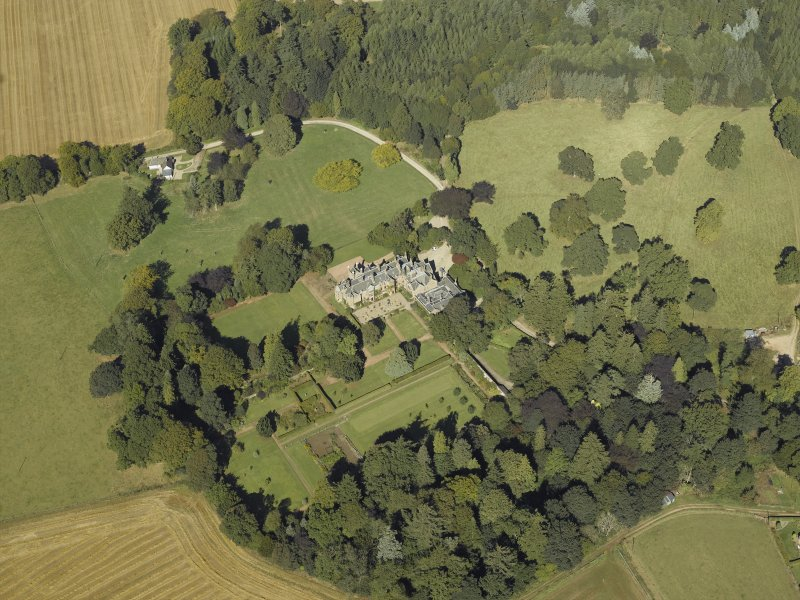 Oblique aerial view centred on the country house and gardens with the cottage adjacent, taken from the S.