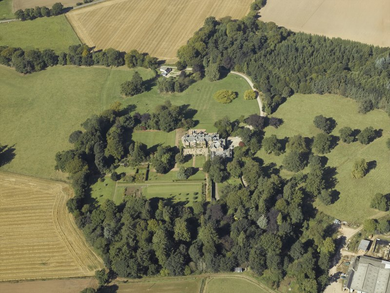 Oblique aerial view centred on the country house and gardens with the cottage adjacent, taken from the SE.