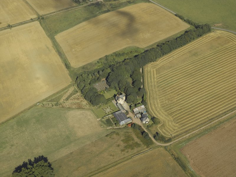 Oblique aerial view centred on the farmhouse, farmsteading and tower-house, taken from the SSW.