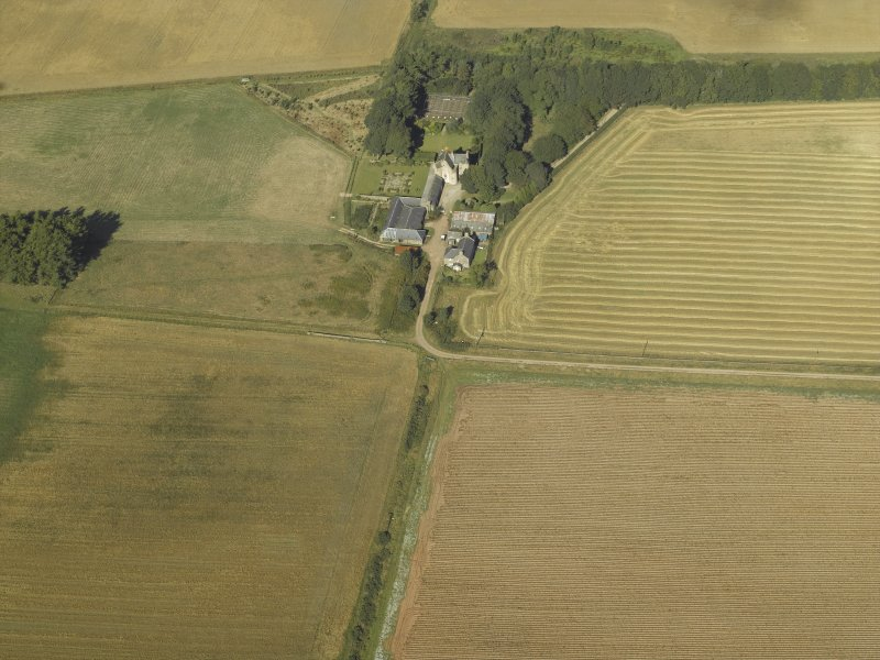 Oblique aerial view centred on the farmhouse, farmsteading and tower-house, taken from the SE.