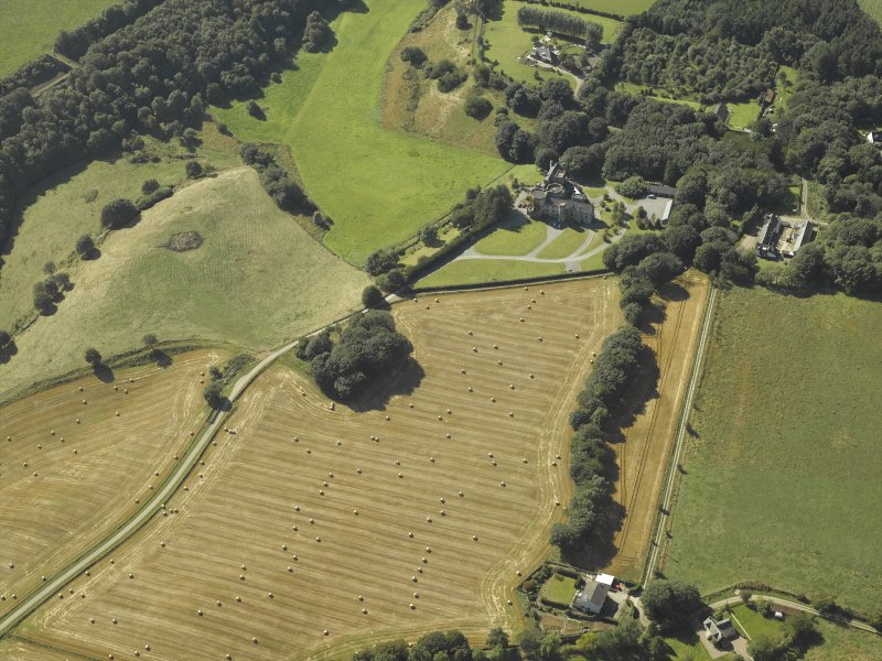 Oblique aerial view centred on the country house, dovecot, summerhouse, gate-lodge and walled garden, taken from the NE.