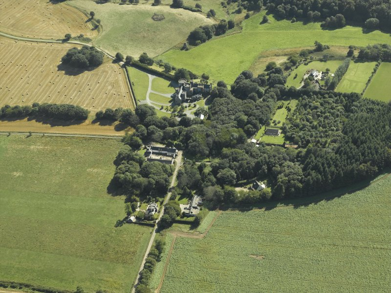 Oblique aerial view centred on the country house, dovecot, summerhouse, gate-lodge and walled garden, taken from the NW.