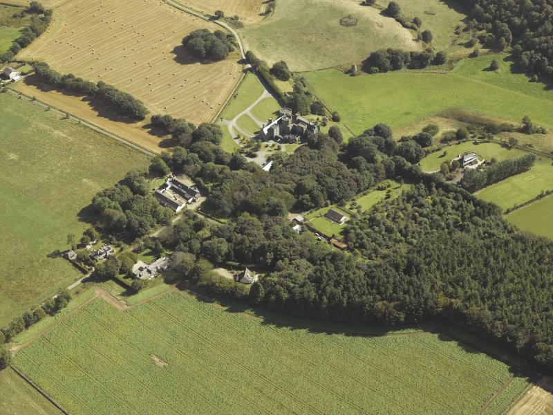 Oblique aerial view centred on the country house, dovecot, summerhouse, gate-lodge and walled garden, taken from the WNW.