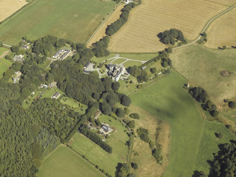 General oblique aerial view centred on the country house, dovecot, summerhouse, gate-lodge and walled garden, taken from the SW.