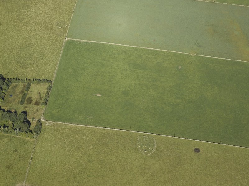 Oblique aerial view centred on the remains of the cairn and stone circle with the remains of the recumbent stone circle adjacent, taken from the SSE.