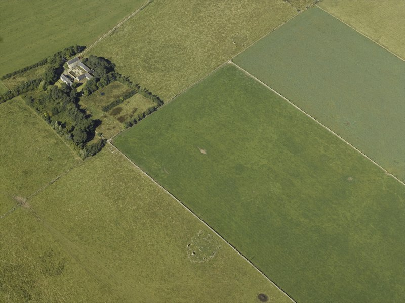 Oblique aerial view centred on the remains of the cairn and stone circle with the remains of the recumbent stone circle adjacent, taken from the SE.