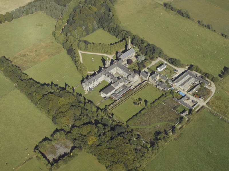 Oblique aerial view centred on the college, church, chapel, dovecot, walled garden and cottage, taken from the SW.