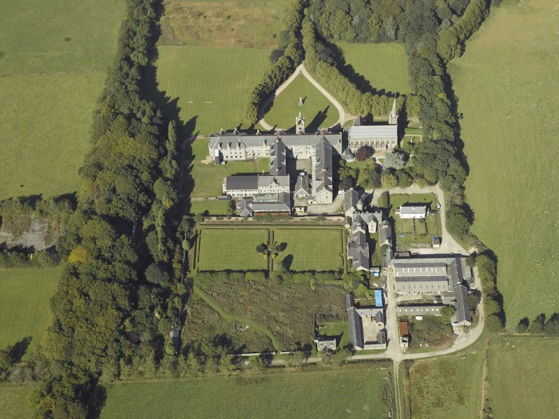 Oblique aerial view centred on the college, church, chapel, dovecot, walled garden and cottage, taken from the SSE.