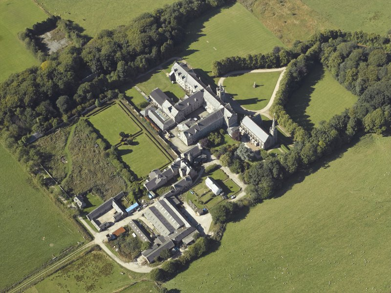 Oblique aerial view centred on the college, church, chapel, dovecot, walled garden and cottage, taken from the E.