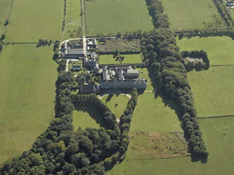 Oblique aerial view centred on the college, church, chapel, dovecot, walled garden and cottage, taken from the N.