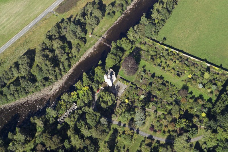 Oblique aerial view centred on the country house, walled garden and suspension bridge, taken from the SW.