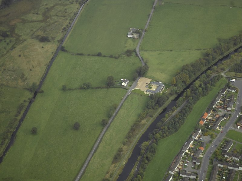 SW oblique aerial view of Auchendavy Roman fort and the course of the Antonine Wall and the military way.