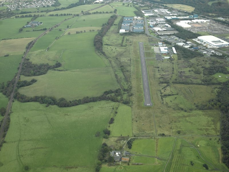 General oblique aerial view centred on the site of the Roman fort, possible Roman fortlet and the course of the Antonine Wall and the Military Way with the airfield and airport adjacent, taken from the W.