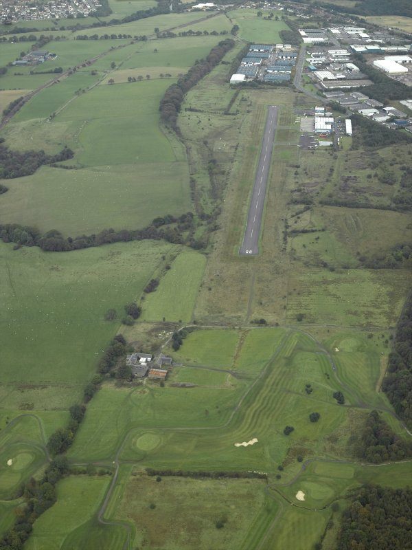 WSW oblique aerial view of Westerwood Roman Fort and possible fortlet, course of the Antonine Wall and Military Way and adjacent Cumbernauld airfield and airport.