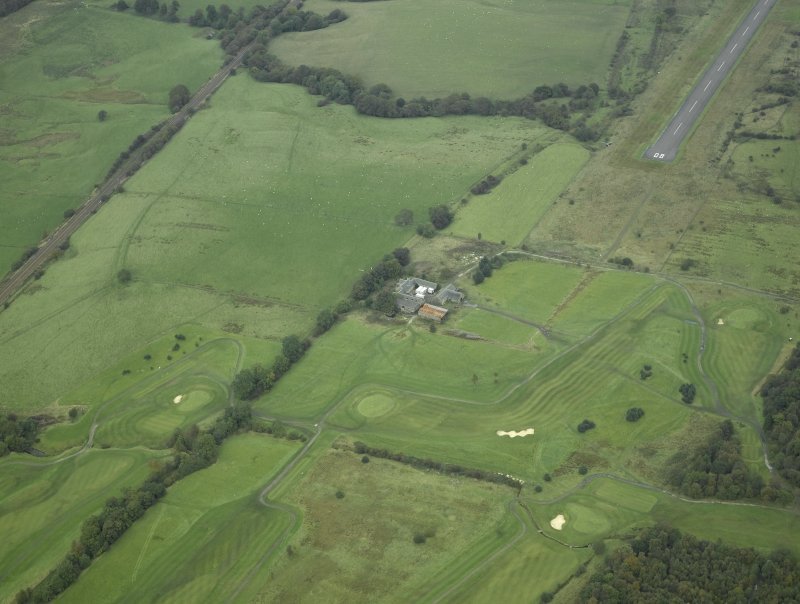 General oblique aerial view centred on the site of the Roman fort, possible Roman fortlet and the course of the Antonine Wall and the Military Way with the airfield and airport adjacent, taken from the SW.