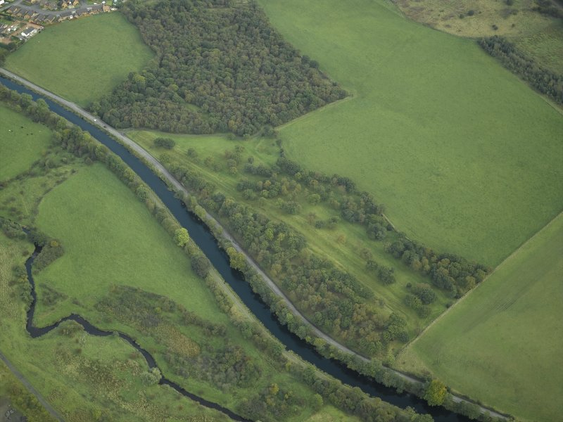 Oblique aerial view centred on the site of the Roman fortlet and the course of the Antonine Wall and the Military Way with the canal and aqueduct adjacent, taken from the WNW.