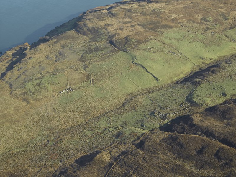 General oblique aerial view centred on the remains of the farmstead, chapel, enclosure, townships, rig and lazy beds, taken from the WSW.