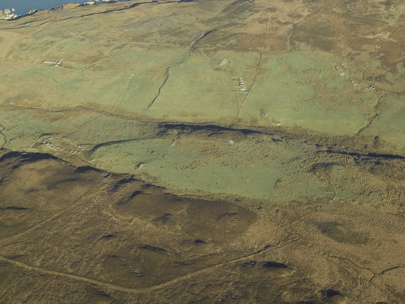General oblique aerial view centred on the remains of the farmstead, chapel, enclosure, townships, rig and lazy beds, taken from the SSW.
