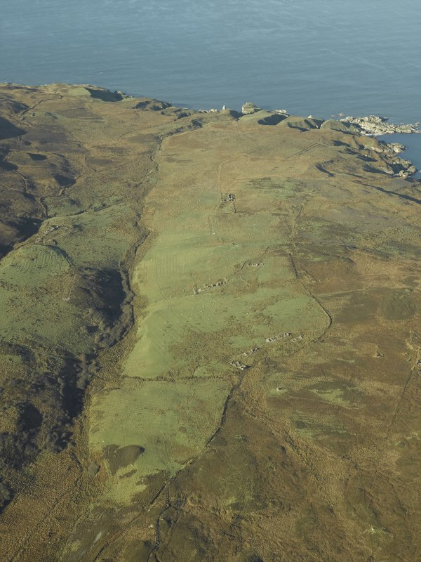 General oblique aerial view centred on the remains of the farmstead, chapel, enclosure, townships, rig and lazy beds, taken from the ESE.
