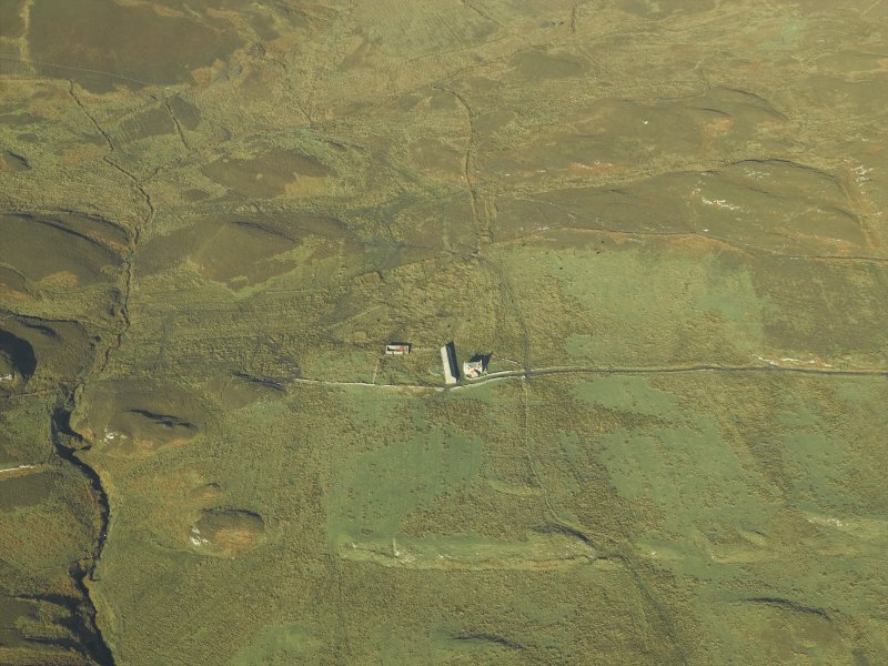 Oblique aerial view centred on the remains of the township and field-system and the farmhouse and farmsteading, taken from the SE.