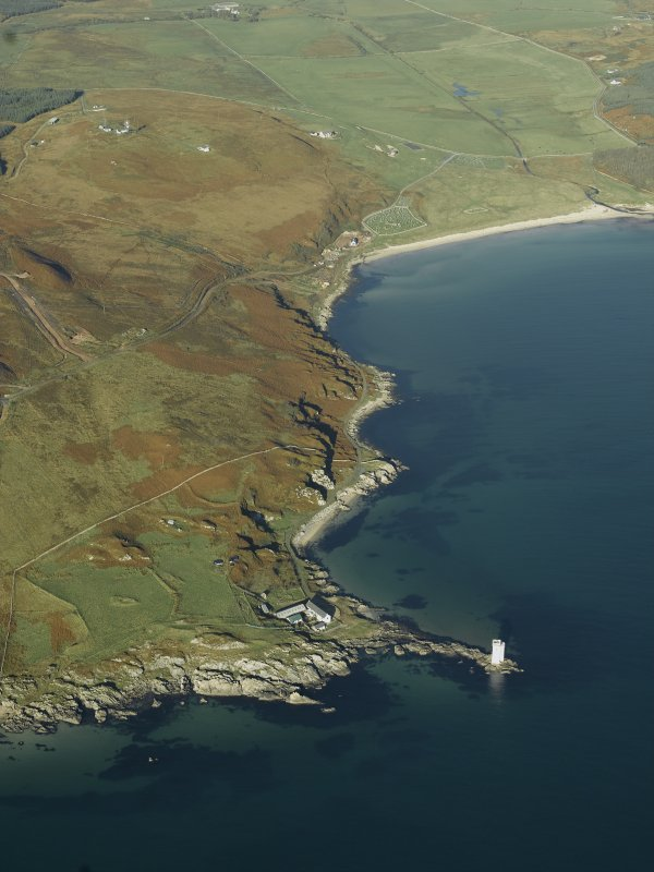General oblique aerial view centred on Carraig Fhada lighthouse, Islay, houses and remains of the clearance cairns, taken from the SE.
