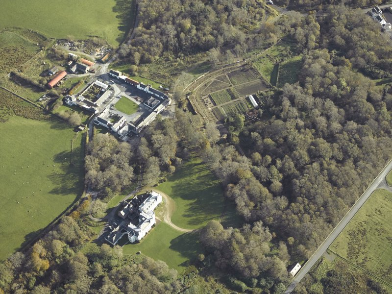 Oblique aerial view centred on the country house, kennels, cottage, farmsteading, byre, farmhouse and walled garden, taken from the WNW.