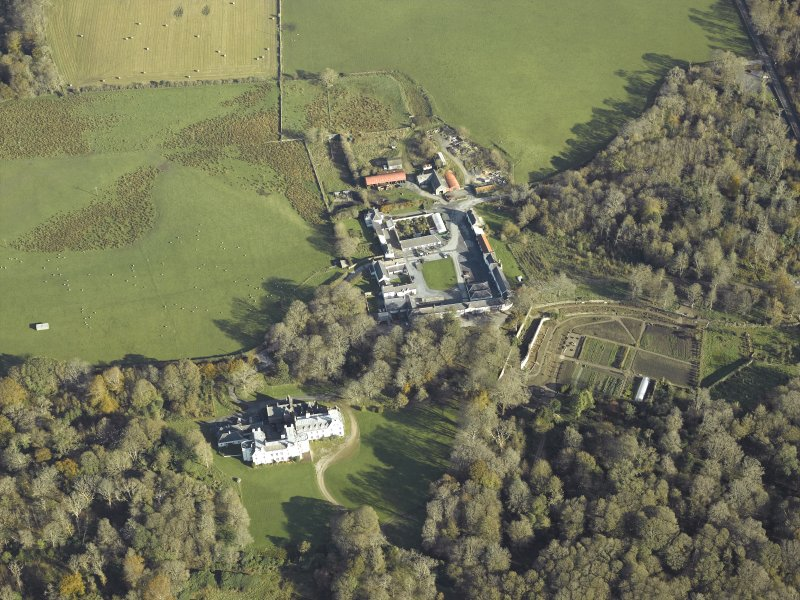 Oblique aerial view centred on the country house, kennels, cottage, farmsteading, byre, farmhouse and walled garden, taken from the WSW.