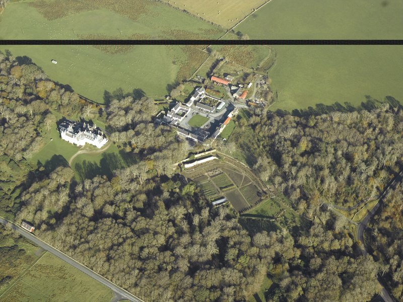 General oblique aerial view centred on the country house, kennels, cottage, farmsteading, byre, farmhouse and walled garden, taken from the SSW.
