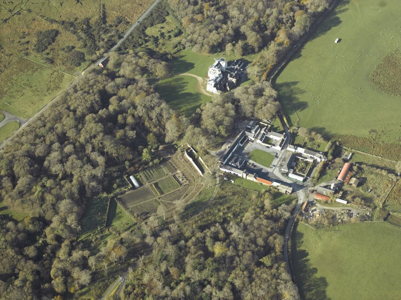 General oblique aerial view centred on the country house, kennels, cottage, farmsteading, byre, farmhouse and walled garden, taken from the E.