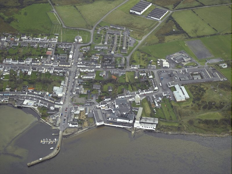 General oblique aerial view of Bowmore village, Islay, centred on the pier, whisky distillery and church, taken from the NW.