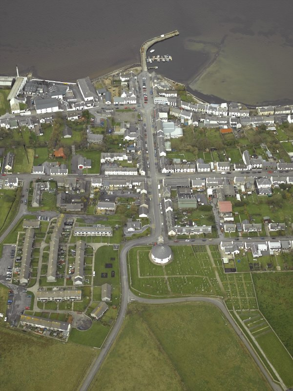 General oblique aerial view of the village centred on the church with the whisky distillery and pier adjacent, taken from the SSE.