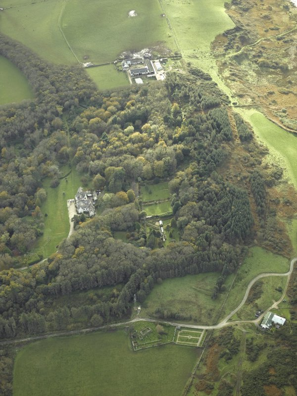 General oblique aerial view centred on the country house and walled garden with the farmsteading and farmhouse and remains of the church and burial-ground adjacent, taken from the NNE.