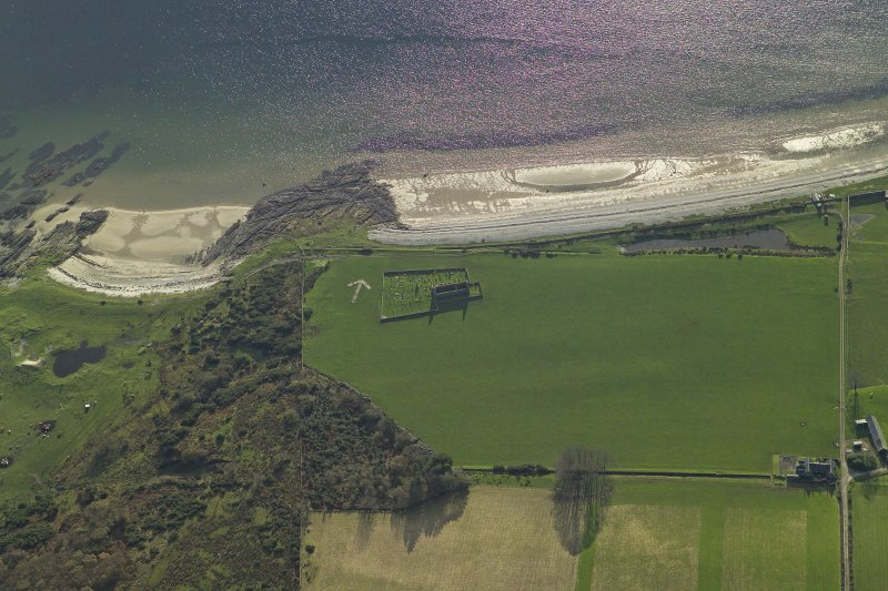 Obique aerial view centred on the remains of the chapel, burial ground and bombing range marker, taken from the NE.