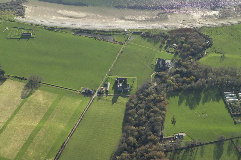 Oblique aerial view centred on the remains of the tower-house with the country house and remains of the church, burial ground and bombing range marker adjacent, taken from the NNE.