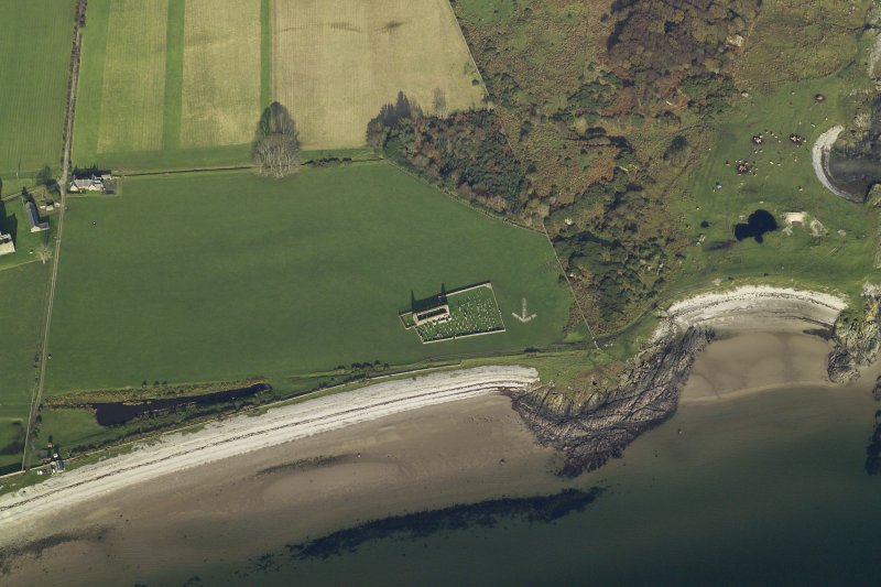 Obique aerial view centred on the remains of the chapel, burial ground and bombing range marker, taken from the SW.
