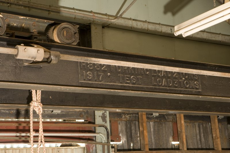 Interior.  Detail of loading stamp with date on overhead gantry crane in engineers machine shop.