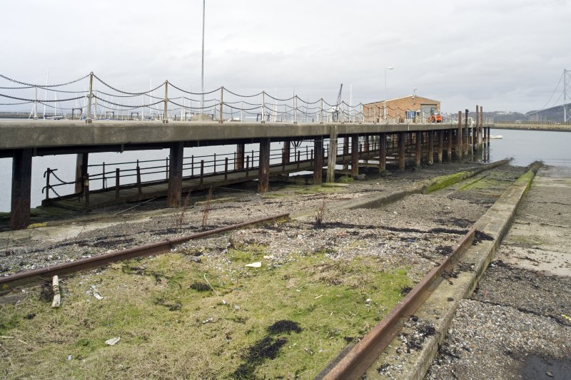View.  Showing slipway adjacent to the rope splicing table and the S end of the E pier with Loop Shed in mid-distance.