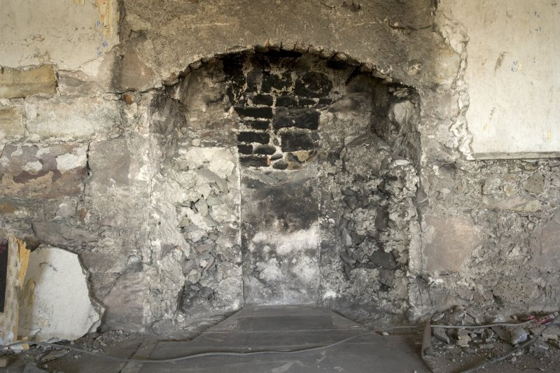 Interior. 2nd floor, NW room, detail of remains of fireplace