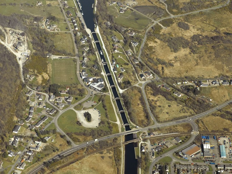 Oblique aerial view centred on the canal at Neptune's Staircase, locks, swing bridges and railway bridge, taken from the SW.