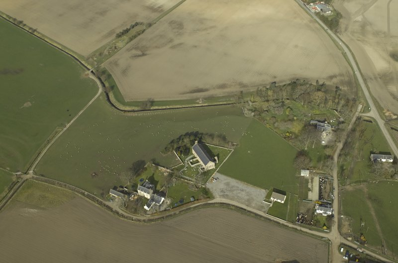 Oblique aerial view centred on the church, burial-ground and the manse, taken from the SE.