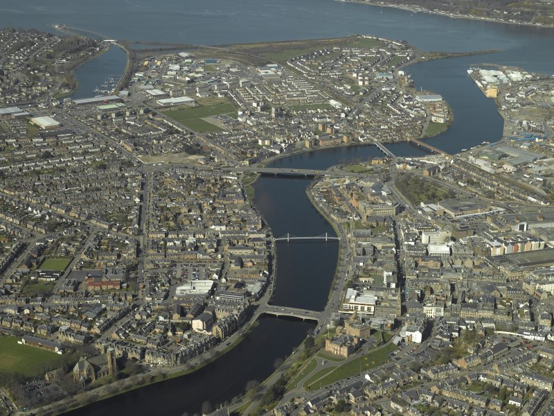 General oblique aerial view of the town centred on the suspension bridges, road bridges and railway viaduct with the castle and prison in the foreground, taken from the SE.