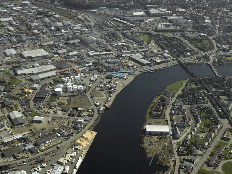 General oblique aerial view of the town centred on the shipyard with the railway viaduct and road bridge adjacent, taken from the NW.