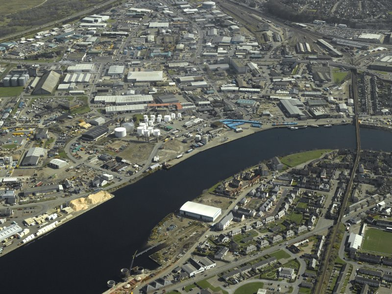 General oblique aerial view of the town centred on the shipyard with the railway viaduct adjacent, taken from the W.