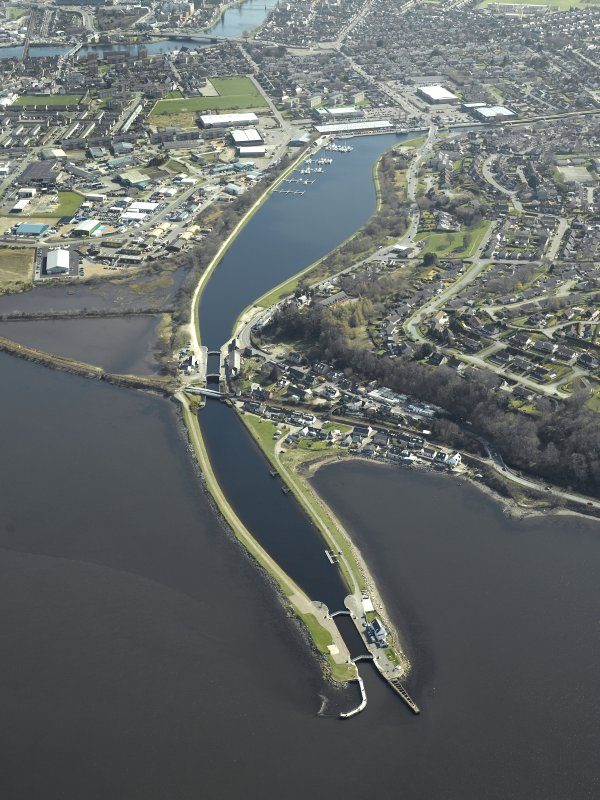 General oblique aerial view centred on the Caledonian Canal, locks, swing bridge and canal basins, taken from the NW.